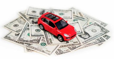 toy car sitting on top of a pile of money
